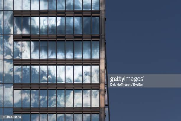 low angle view of glass building against sky - fensterfront stock-fotos und bilder