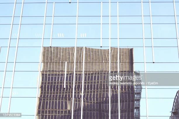 low angle view of glass building against sky - japonês stock pictures, royalty-free photos & images