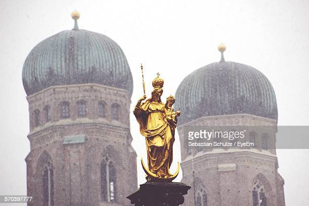 Low Angle View Of Gold St Marys Statue Against Frauenkirche Towers In Marienplatz