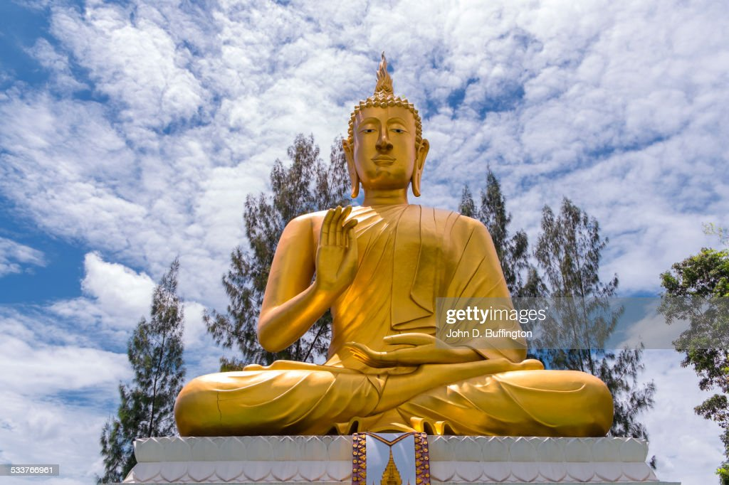 Low angle view of golden Buddha statue under cloudy sky : Foto stock