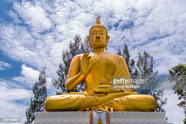 low angle view of golden buddha statue under cloudy sky - buddha foto e immagini stock