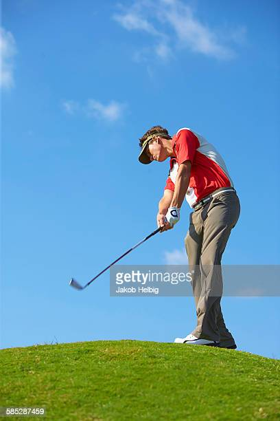 Low angle view of golfer on hill wearing sun visor holding golf club