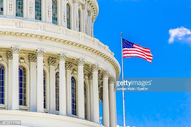 low angle view of government building and american flag against blue sky - ciudades capitales fotografías e imágenes de stock