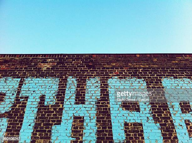 Low Angle View Of Graffiti On Brick Wall Against Clear Sky