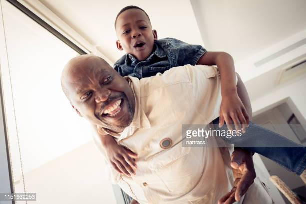 low angle view of grandfather piggybacking boy - grandfather stock pictures, royalty-free photos & images