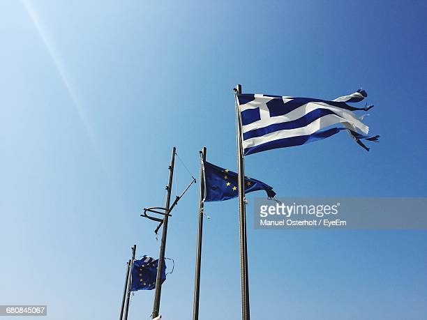 Low Angle View Of Greek And European Flags Against Clear Blue Sky