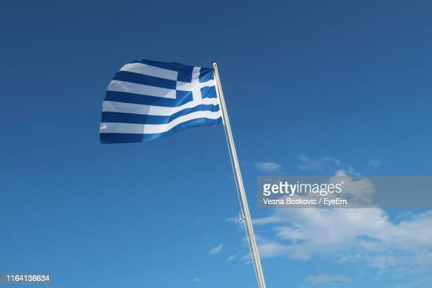 low angle view of greek flag against blue sky - greek flag stock pictures, royalty-free photos & images