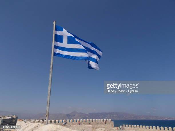 low angle view of greek flag against clear blue sky - greek flag stock pictures, royalty-free photos & images