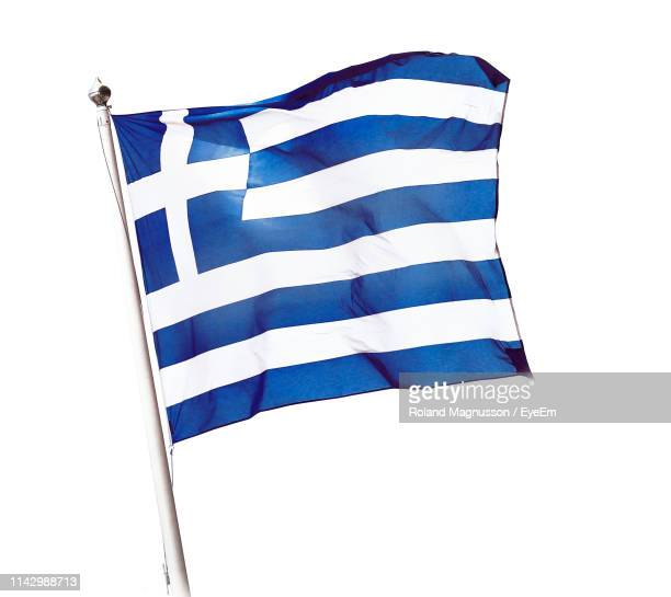 low angle view of greek flag against white background - greek flag stock pictures, royalty-free photos & images