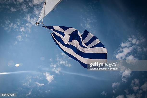 Low Angle View Of Greek Flag Fluttering Against Blue Sky
