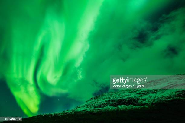 low angle view of green mountain against sky at night - aurora vargas stock pictures, royalty-free photos & images