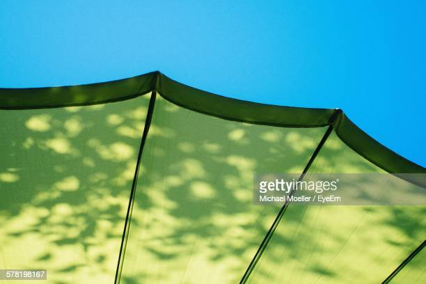Low Angle View Of Green Parasol Against Clear Blue Sky
