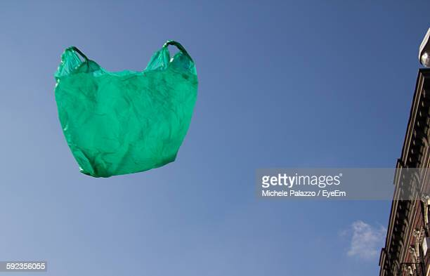 Low Angle View Of Green Plastic Bag In Mid-Air Against Clear Blue Sky