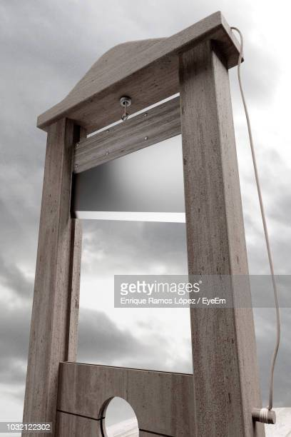 low angle view of guillotine against cloudy sky - guillotine photos et images de collection