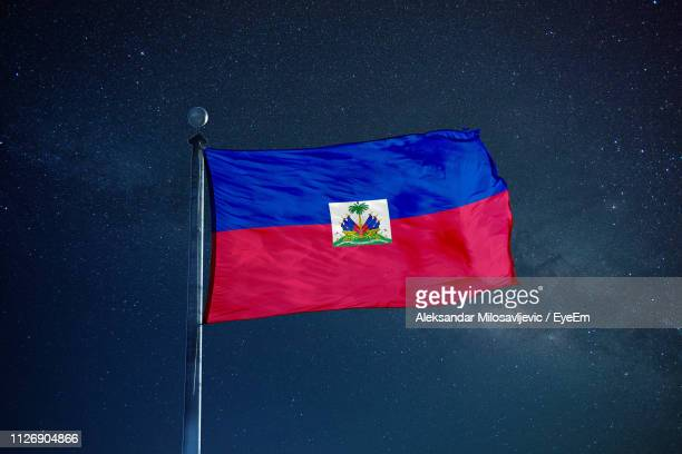 low angle view of haiti flag against star field sky - haitianas fotografías e imágenes de stock