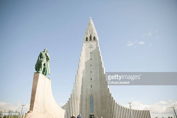 Low angle view of Hallgrmskirkja and statue, Reykjavik, Iceland