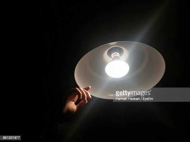 Low Angle View Of Hand And Illuminated Pendant Light Against Black Background