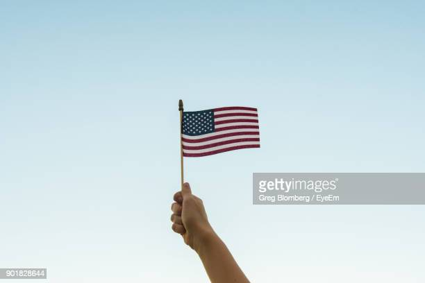 Low Angle View Of Hand Holding American Flag Against Clear Sky