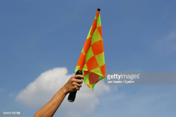 low angle view of hand holding flag against blue sky - 審判員 ストックフォトと画像
