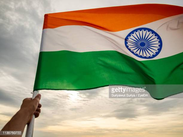 low angle view of hand holding indian flag against sky - indian flag stock pictures, royalty-free photos & images