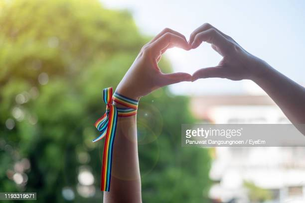 low angle view of hands creating heart shape outdoors - pride stock pictures, royalty-free photos & images
