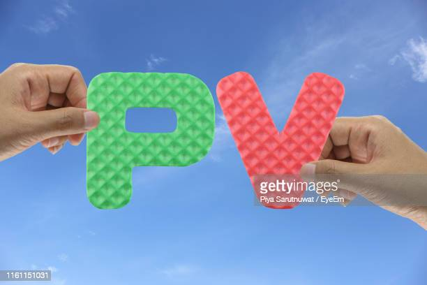 low angle view of hands holding alphabets against sky - letter p stock pictures, royalty-free photos & images