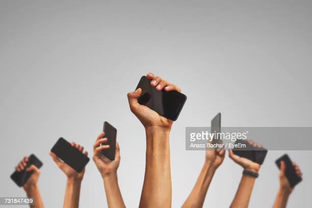 low angle view of hands holding mobile phone against white background - middelgrote groep mensen stockfoto's en -beelden