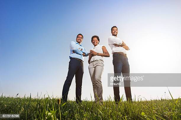 Low angle view of happy business colleagues with crossed arms.