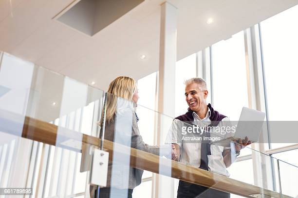 Low angle view of happy business people shaking hands at hotel lobby