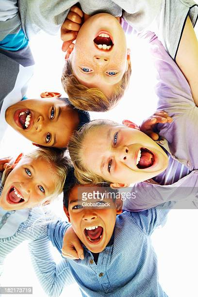 Low angle view of happy children huddling together