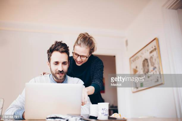 Low angle view of happy couple looking at laptop in domestic room