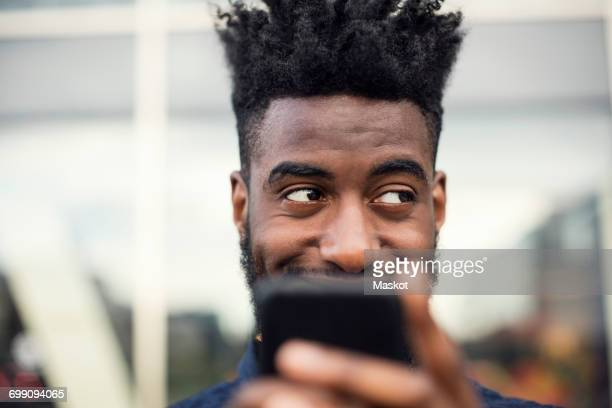 Low angle view of happy man using smart phone while looking away