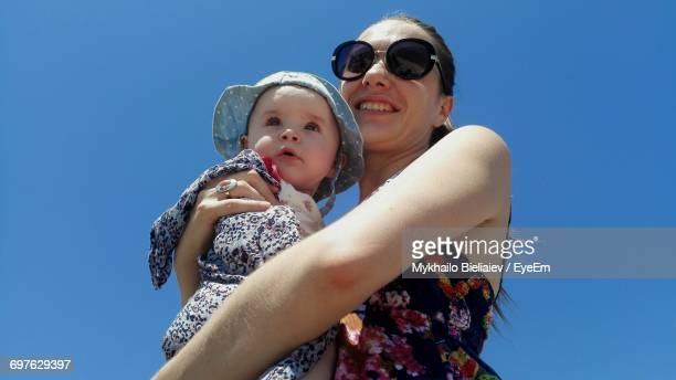 Low Angle View Of Happy Mother Holding Daughter Against Clear Blue Sky