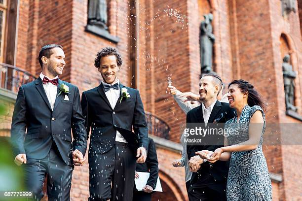 Low angle view of happy newlywed gay couple walking while friends throwing confetti