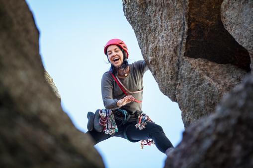 Low angle view of happy woman rock climbing - gettyimageskorea
