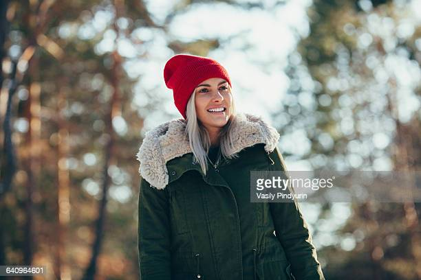 Low angle view of happy young woman wearing knit hat and jacket while looking away