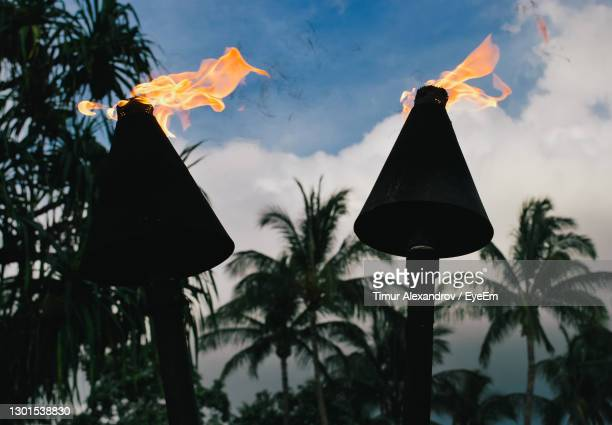 low angle view of hawaiian tiki lanterns hanging against sky during sunset - hawaii flag stock pictures, royalty-free photos & images