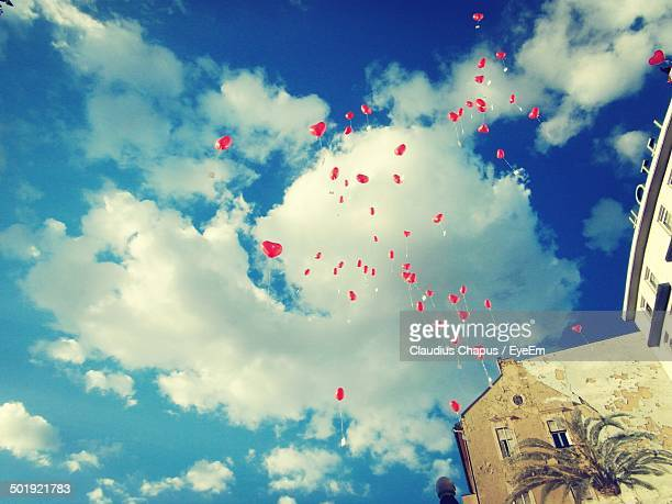 Low angle view of heart shape balloons flying against cloudy sky
