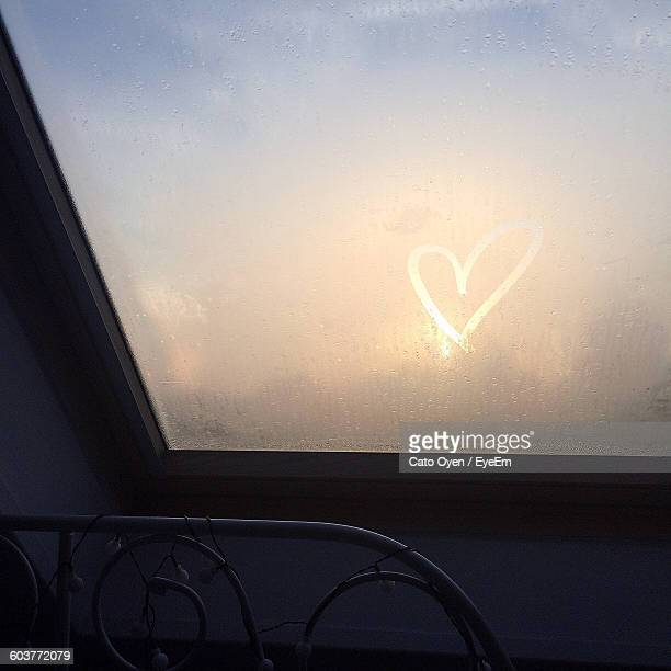 Low Angle View Of Heart Shape Made On Condensed Skylight During Sunset
