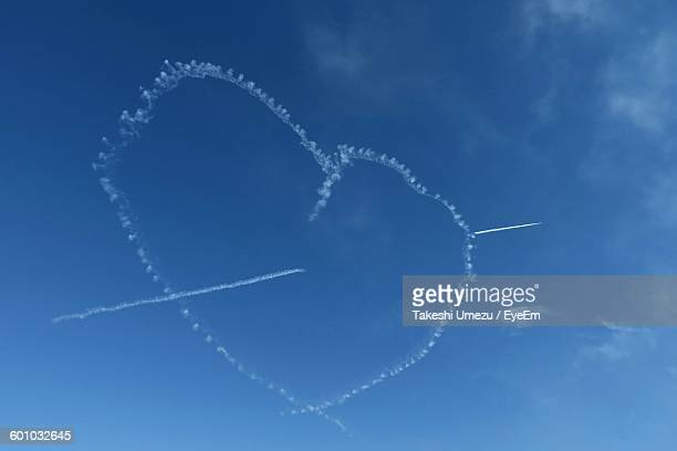 Low Angle View Of Heart Shape Vapor Trail In Blue Sky