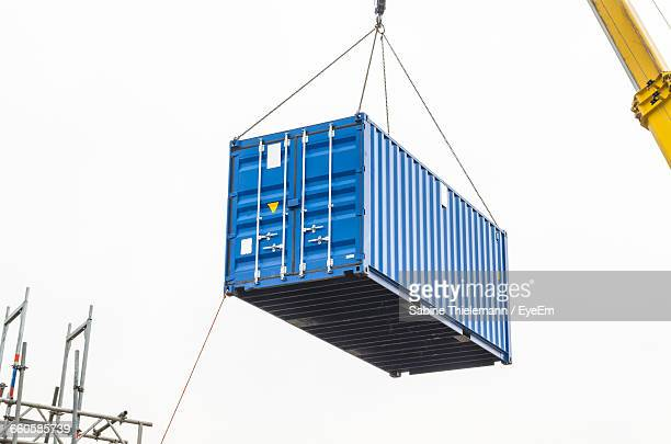 low angle view of heavy container against clear sky - cargo container stock pictures, royalty-free photos & images