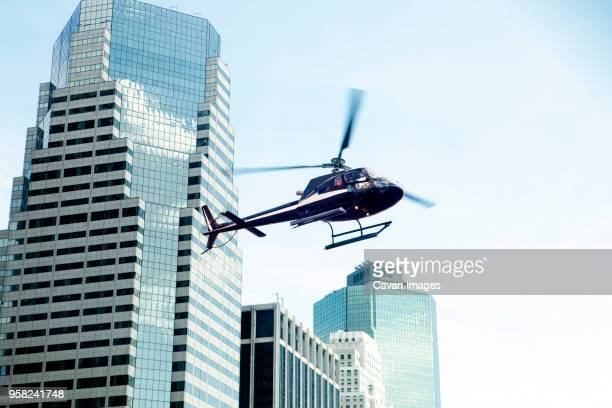 low angle view of helicopter against modern buildings in city - helicopter photos stock pictures, royalty-free photos & images