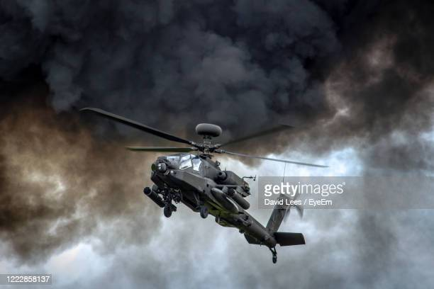 low angle view of helicopter against sky - apache helicopter stock pictures, royalty-free photos & images