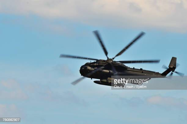 low angle view of helicopter flying against sky - プロペラ ストックフォトと画像