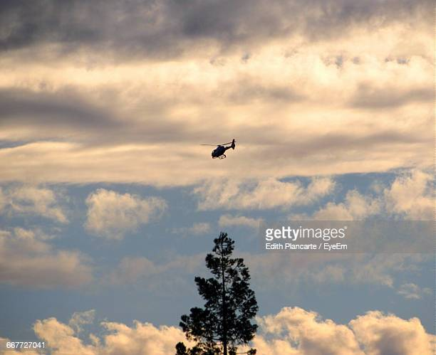 low angle view of helicopter flying in cloudy sky - helicopter photos stock pictures, royalty-free photos & images