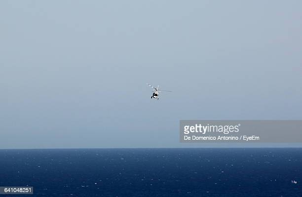 low angle view of helicopter flying over blue sea against clear sky on sunny day - helicopter photos stock pictures, royalty-free photos & images