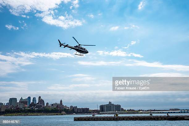 Low Angle View Of Helicopter Flying Over Lake Against Sky In City