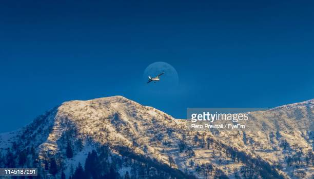 low angle view of helicopter flying over snowcapped mountains against clear blue sky - locarno stock photos and pictures