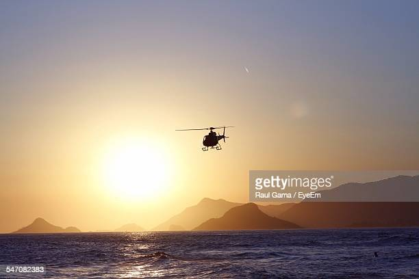 Low Angle View Of Helicopter Over Sea In Front Of Mountains During Sunset