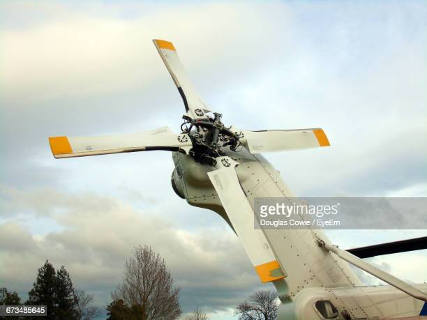 low angle view of helicopter propeller against cloudy sky - helicopter photos stock pictures, royalty-free photos & images